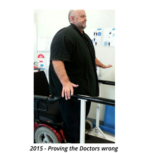 Geoff Hughes proving the doctors wrong standing in parallel bars from wheelchair