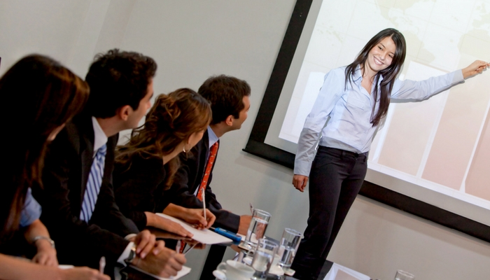 resilience is essential for leaders - meeting woman pointing to presentation in a boardroom